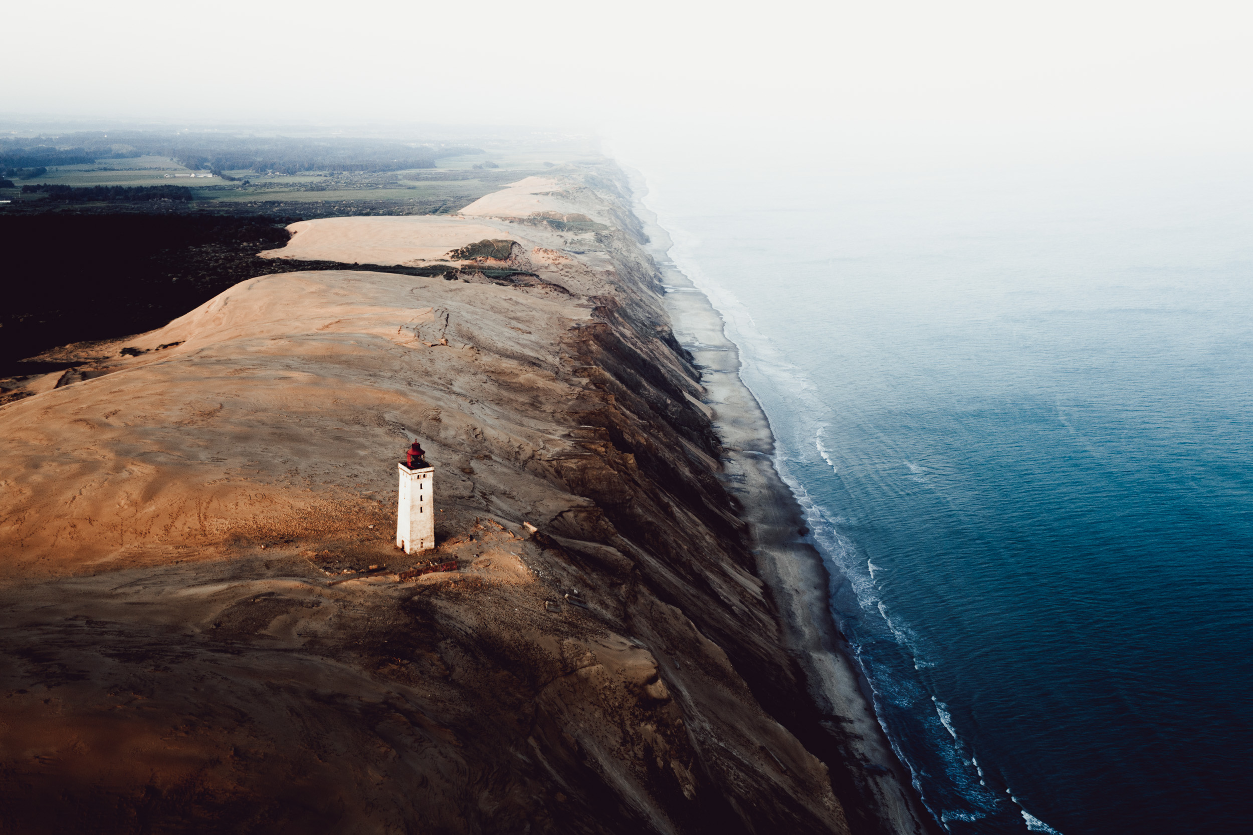 Picture shows old white lighthouse on sanddune near the ocean coast from above.
